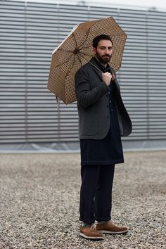 I like the way the umbrella compliments the rest of the outfit. I hate those rolled-up pants. Interesting extended shirt.