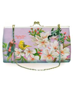 """Beautiful clutch bag with attached silver shoulder chain from the Woody Ellen Bloom collection. Rigid design with soft padded microfiber to front and back with a pretty bird and floral illustration to front and back (black satin sides to bag). Silver metal twist lock fastening. Black satin interior with side open pocket. Approximate Measurements: Width 9"""" (23cm), Height 5"""" (12.5cm), Depth 2"""" (5cm) Matching purse available. Woody Ellen is a Belgian illustrator and figurative painter. She…"""