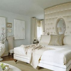 "Boudoir Glamour  In the master suite, a tufted mini wall covered in ivory satin extends the upholstered luxury of the king-size bed all the way to the ceiling. The creamy color scheme gives the room maximum Hollywood glamour.  Several large windows illuminate the room. ""I don't think you can have too much natural light in a house,"" architect Harrison says."