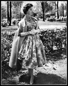 Model is wearing party dress in delicate mauve print, the cape-coat is adorned with large pointed collar in the back, by Carven, photo by Georges Saad, 1957