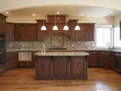 wood floor, dark cabinets, lighter tan or brown counter