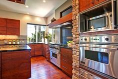A wall of built-in stainless steel ovens in this rustic Zen kitchen allows the cook to prepare food in a timely and efficient manner. Warm wood cabinets pair with black granite countertops for a look that combines rustic and Asian styles.