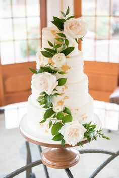 The Sutherland Wedding Photos by Mikkel Paige Photography. White tiered buttercream cake with gold leaf and cascading white roses and greenery by Ashley Cakes NC. Planning by A Southern Soiree.