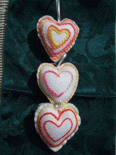 """Heart handmade white felt hearts. Set of 3 white felt hearts ideal gift. Each heart is individually made by myself, and each design is unique. No two are the same.  Hand embroidered with lovely ribbon handles.    1 heart has a red felt back.    The stuffing is for childrens toys.    Size 3.5"""" x 3.5"""" / 9cm x 9cm"""