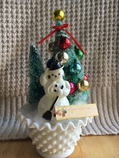 This vintage inspired Christmas scene set in hobnail style milk glass is the perfect piece of holiday decor for any kitschy home this holiday season. Vintage plastic snowman is set amongst a mini forest of bottle brush trees adorned with vintage miniature Christmas ornaments. Mr. Snowman does have discoloration and markings to show his age, but a few touch ups to his paint and hes still dapper as ever! The milk glass figurine combo makes this piece the perfect mix of kitsch and class