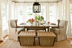 Mix the seating for a collected look.  A combination of styles including wing chairs, a curvy settee, and burlap-topped benches circles the dining table.  Dress a r