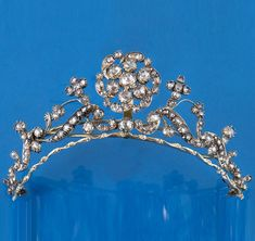 A GEORGIAN DIAMOND TIARA. The scrolling foliate openwork design is set overall with graduated rose-cut diamonds, in silver and gold closed back settings, the central flowerhead set en tremblant, 11.5cm. wide.
