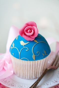 """Love Birds"" Cupcake --- Tiny birds perched on swirling branches motif done in raised gold leaf atop royal blue fondant with a pink flower. Pure beauty."
