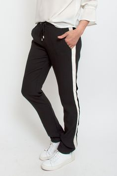 These wide-leg trousers are sure to become a staple for casual days. The black stretch material makes this pair extra comfortable for a laid-back look of luxe. It features ecru athleticwear-inspired stripes on the sides, an elasticated waistband and side pockets. Wear yours with a blazer for sophisticated balance. By Mbym.      Available at Sienna Boutique.