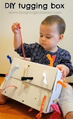DIY tugging box for young toddlers. When they pull at one end it lengthens and shortens the ribbon at the other. Great for learning cause and effect and problem solving. Laughing Kids Learn