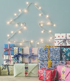 String up some fairy lights in the shape of a tree, then pile your wrapped presents underneath it.