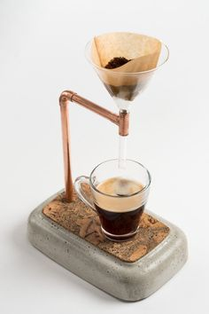 Coffee Maker for purists. Just make a coffee. Filter and coffee in the glass funnel, hot water and ready! It will be a highlight in your kitchen and office.   Product details   - Coffee Maker made of concrete and copper  - circa 34 cm high, 15 cm wide, 23 cm length  - weight ca. 3 kg  - surface with natural cork  - concrete surface sealed to protect against stains  - with rubber feet  - incl. separate glass funnel  - handmade in Germany   Note   - for cups and glasses with 9 - 10 cm height…