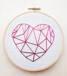 A geometric heart with a pink ombre design is embroidered by me with light tan muslin fabric and different shades of pink embroidery flosses into