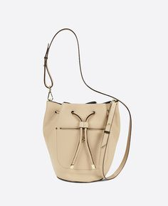 """Bucket list: think big and carry on with our traffic-stopping signature mini bucket bag. Drawstring closure. 42"""" adjustable leather shoulder strap. Front pocket with interior snap closure. 11""""W x 9""""H x 6""""D."""