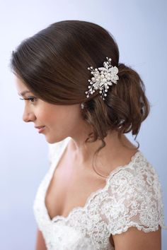 Pearl Leaf Clip is intricately designed to be a soft elegant accent for your bridal hairstyle. This hair clip has a polished silver finish and features rhinestone embellished leaves. Hand-wired rhinestones and soft white simulated pearls form delicate branches on the clip. Coordinates with both ivory and white bridal gowns. The hair clip measures approximately 3  inches x 2  inches at its widest point. This accessory secures easily to the hair with an alligator clip on the back.  Pearl Leaf…