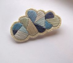 Gray cloud geometric brooch hand embroidered with a silver lining. $25.00, via Etsy.