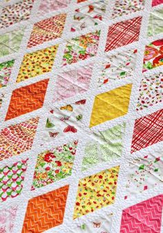 "Set against a crisp and clean white background, every print in Clementine POPS in this quilt! Pattern is from the book ""Modern Designs for Classic Quilts"" by Kelly Biscopink & Andrea Johnson. Quilt measures 44″ x 58.""Fabric collection: ClementineQuilt made by: Holly DeGroot of the blog..."