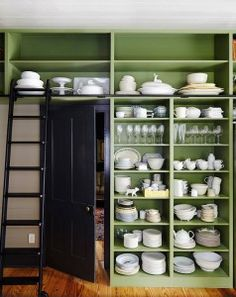 Kitchen with open shelf wall cabinet. Puttnam rolling ladder makes tall shelves accessible. Benjamin Moore Land of Liberty paint color. Door and trim is Benjamin Moore Nightfall. #BenjaminMooreLandofLiberty #BenjaminMooreNightfall Tim Cuppett Architects.
