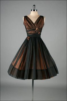 """1950's Black and Bronze Cocktail Dress"" Would be great without the rose ""decoration"" that reminds me too much of our ""funeral choir dresses"" in school. Otherwise, this dress is exactly my style!"