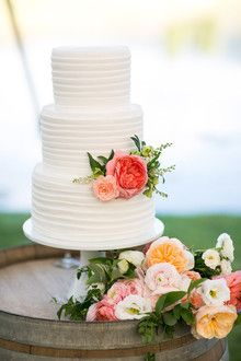 White pleated wedding cake with fresh florals, by  D'Elissious Cakes.