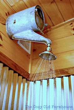 A creative shower head using a watering can!  Many other repurposed cabin…