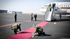 German Chancellor Angela Merkel had to wait on the gangway of her plane after landing at Prague airport, while soldiers adjusted the red carpet.
