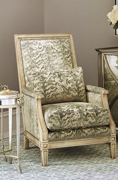 The Fez Chair boasts a carved frame, ornamental nailhead trim and decorative piping on the cushions.