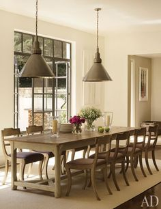 The kitchen's dining area features an antique Swedish pine table with Regency chairs; the pendant lights are by James Huniford Collection.