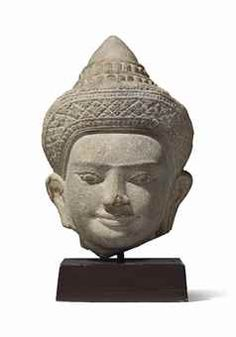 A SANDSTONE HEAD OF VISHNU CAMBODIA, KHMER, ANGKOR WAT PERIOD, 12TH CENTURY Carved with enigmatic expression, with gently smiling and pouting lips, almond-shaped eyes below ridged eyebrows, wearing an elaborate crown carved with rosettes, on wood stand 11 in. (28 cm. high)