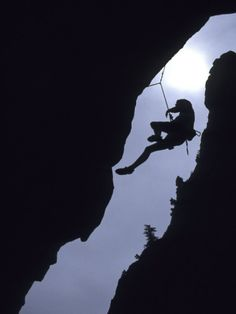 Silhouette of Rock Climber Hanging from Cliff Face Photographic Print at Art.com