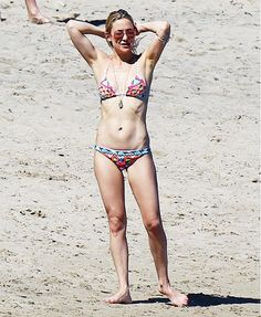 Kate Hudson wears a printed two-piece swimsuit, aviator sunglasses, and several thin body chains