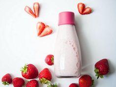 Flasche mit Erdbeer-Mandelmilch; daneben Herzen aus Erdbeeren dekoriert.