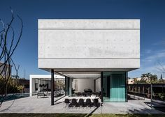 A solid concrete volume sits above the predominantly glazed ground-floor living areas of this house in Israel