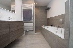Deze badkamer met schuine muur werd handig ingericht met een bad, een ruim lavabomeubel en een onderhoudsvriendelijke inloopdouche. Meer over dit project.