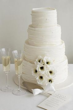 The thin petals of sugar anemones highlight the overlapping layers of fondant on this four-tiered wedding cake.