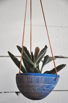 Add a touch of greenery to any space with this decorative hanging planter. The white earthenware hanging vessel is hand pinched, shaped, smoothed,