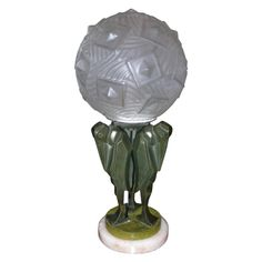 1925 Table Lamp by Artus, in pressed and molded glass; base in green patinated bronze representing three marabouts.