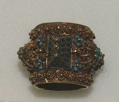 16th century.  Gold Jewish marriage ring, the bezel formed as a high pitched roof with blue enamelled tiling covering an inner hinged lid to a box, beneath engraved in Hebrew Mazal tov (good luck), the hoop decorated with five rosettes of open filigree work topped by a five-petalled flower in blue enamel, and a hanging corded ring. On each side is a border of small rosettes between corded work
