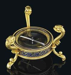Notes from a previous pinner: A JEWELLED TWO-COLOUR GOLD-MOUNTED AND GUILLOCHÉ ENAMEL TABLE COMPASS BY FABERGÉ, WORKMASTER'S MARK OF MICHAEL PERCHIN, ST PETERSBURG, 1899-1903 Circular, raised on three dolphin feet with cabochon ruby eyes, the body enclosing a pivoting gold-mounted compass, the mount enamelled in translucent royal blue on a guilloché ground with gold Vitruvian scroll and stylised water lily leaf paillons.