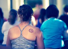 "Tattoo on Misty Scholz depicts a lotus flower with eight petals representing the eighth chakra, the ""Om"" symbol, and warm colors for her Bikram focus."