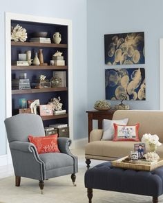Cool blues and pops of coral bring the colors of the sea into your living room. Favorite photos add one-of-a-kind style in this Coastal Living Room design. | Shutterfly