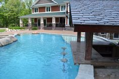 Concrete stools at swim up bar in a Hybrid Swimming Pool with a rustic pool house/outdoor kitchen.