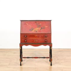 This secretary desk is featured in a solid wood with a red paint finish. This European style workstation has a drop front desk with storage cubbies, 2 spacious drawers, carved trim, and floral accents. Perfect for storing important paperwork! #european #desks #secretarydesk #sandiegovintage #vintagefurniture
