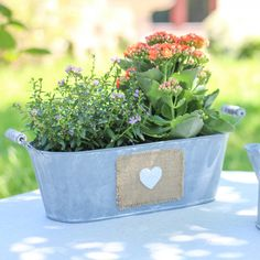 A distressed style planter ideal for a windowsill or out in the garden this item will sit pretty wherever it is placed. Suitable to hold multiple plants this is a eye catching feature to any room in the home or placed outdoors. Made from zinc with a washed grey coating this item features a hessian patched to the front with a hessian patch and small white heart attached. Planter also features two wooden handles to either side for easy transportation when filled with your favourite plants…