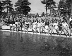 Show girls from the Mikado theater in Tokyo, their legs crossed and bare feet dangling near the water, pose on the side of a swimming pool at a new American air base at Yokota, Japan on August 17, 1946. How one male, presumably a soldier, got into the otherwise all-girl lineup at poolÂ's edge was not explained. Uniformed soldiers stand behind the girls. (AP Photo/Charles Gorry)
