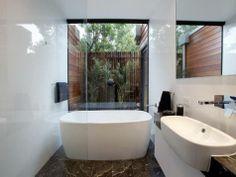 long vanity running up to the bath, half length frameless glass shower screen
