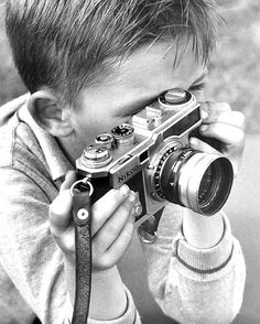 susiesnapshot:    Nikon camera, 1962. Behind camera, kid, boy, child, Nikon, analogue, cute, nuttet, history, hands, focus, concentration, photograph, photo b/w.