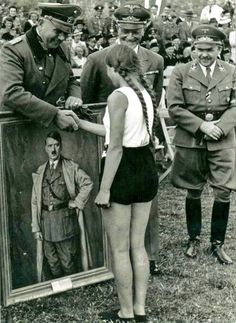 German government officials award a young girl a portrait of the Führer following her win in an athletic competition held by the League of German Maidens, a government-sponsored youth organization opposite the Hitler Youth in terms of gender.