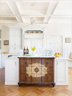 Kitchen - I dream of having this stunning island, which captures all the attention in this dramatic all-white kitchen. From tall, beamed ceilings to parquet-patterned wooden floors, this kitchen is both sophisticated and inviting, and is the perfect atmosphere for this stunning island. I love that the dresser was incorporated into the rest of the island with the use of the same marble counter top.