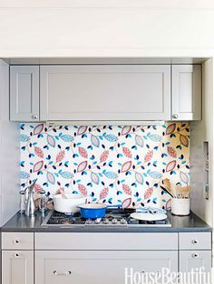 English Country Style Kitchen - House Beautiful.  I wouldn't choose this particular fabric, but what a cool idea.  Fabric behind glass for a backsplash!  Why didn't I think of that!